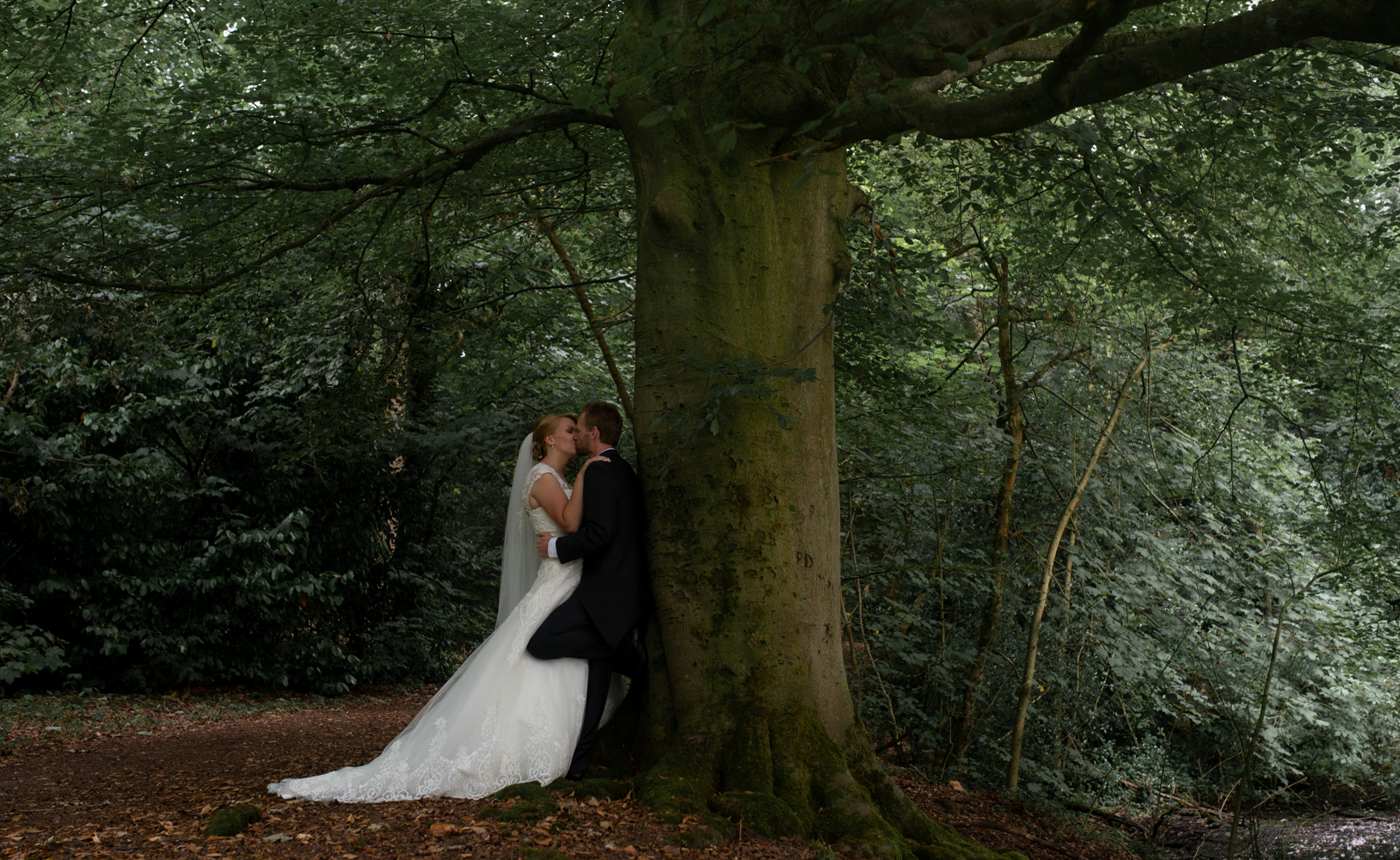 The bride and groom standing in the woods