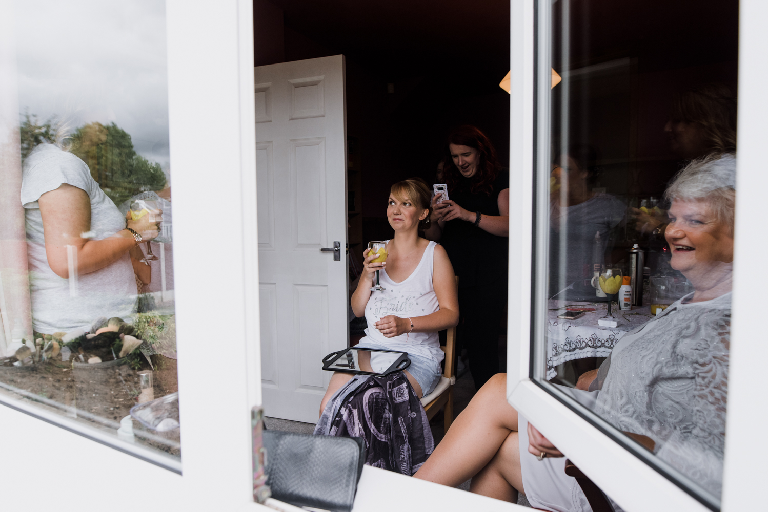 The bride sitting having her makeup and hair done shot through an open window