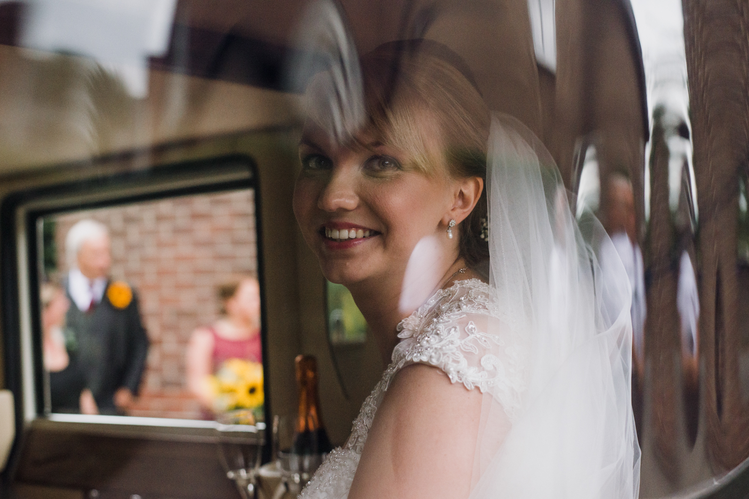 The bride sitting in the back of the car as she arrives at church