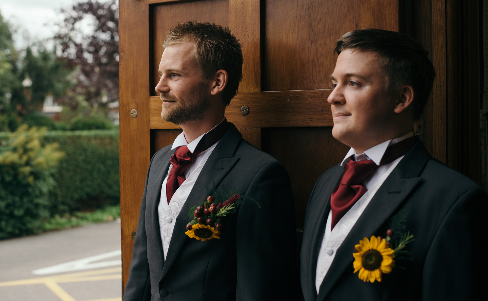 The groom and best man standing in the church doorway welcoming guests