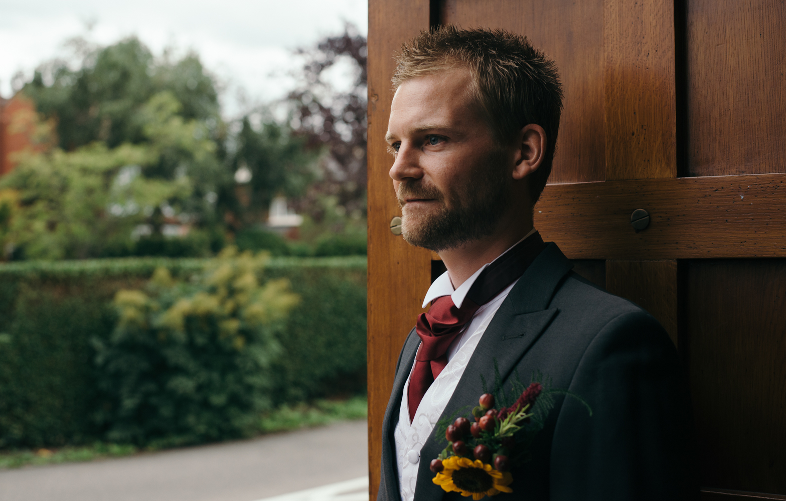 The groom standing welcoming family and guests at the church