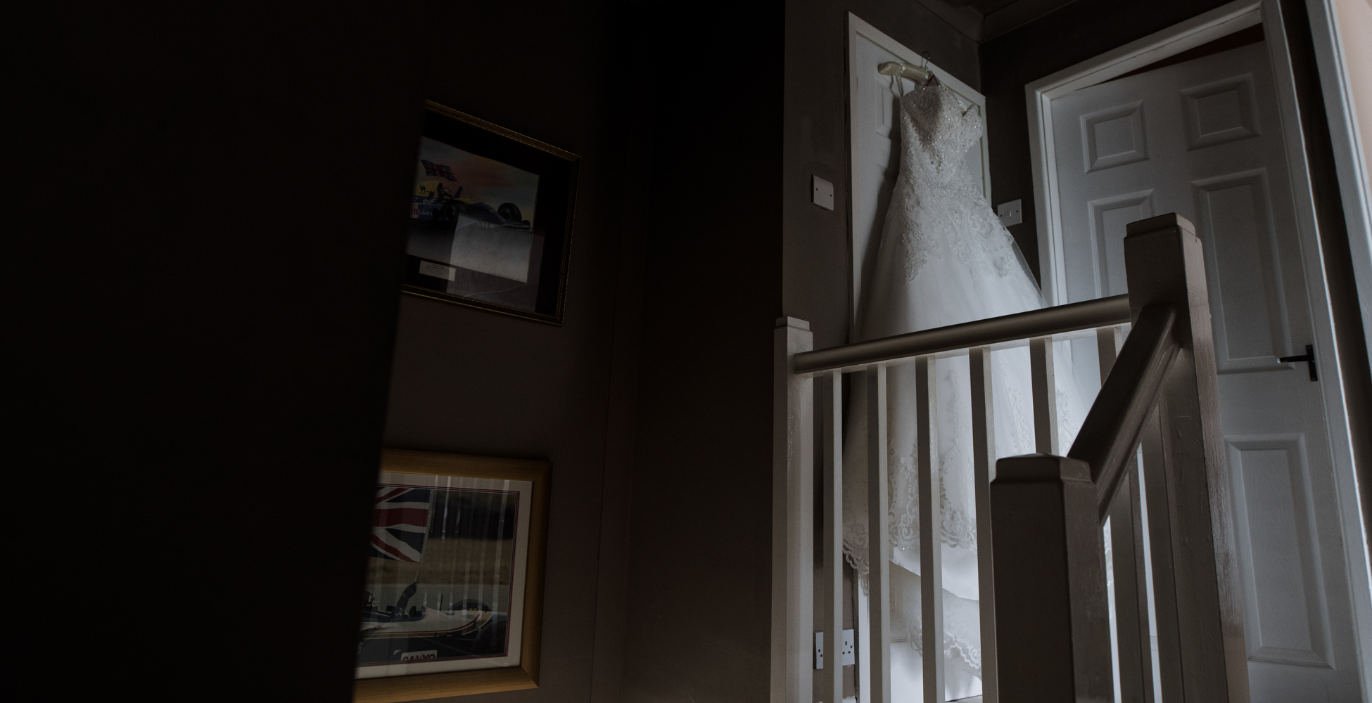 Wide angle photo of the wedding dress at the top of the stairs