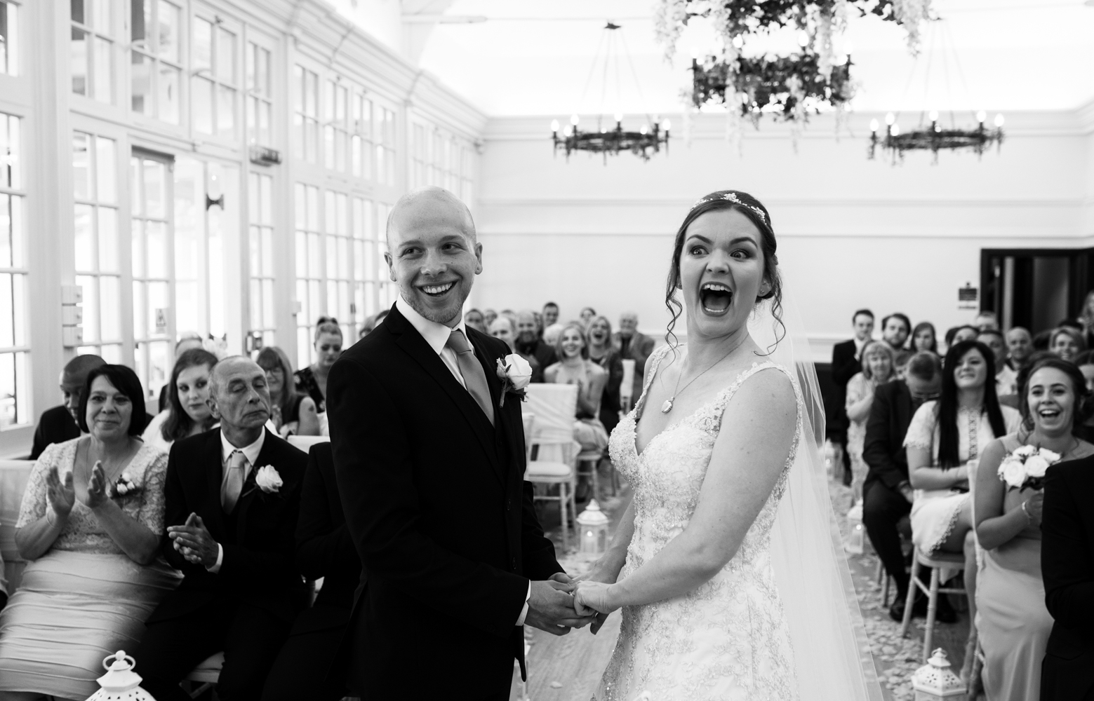 A black and white image of the bride and groom just as the groom says I do