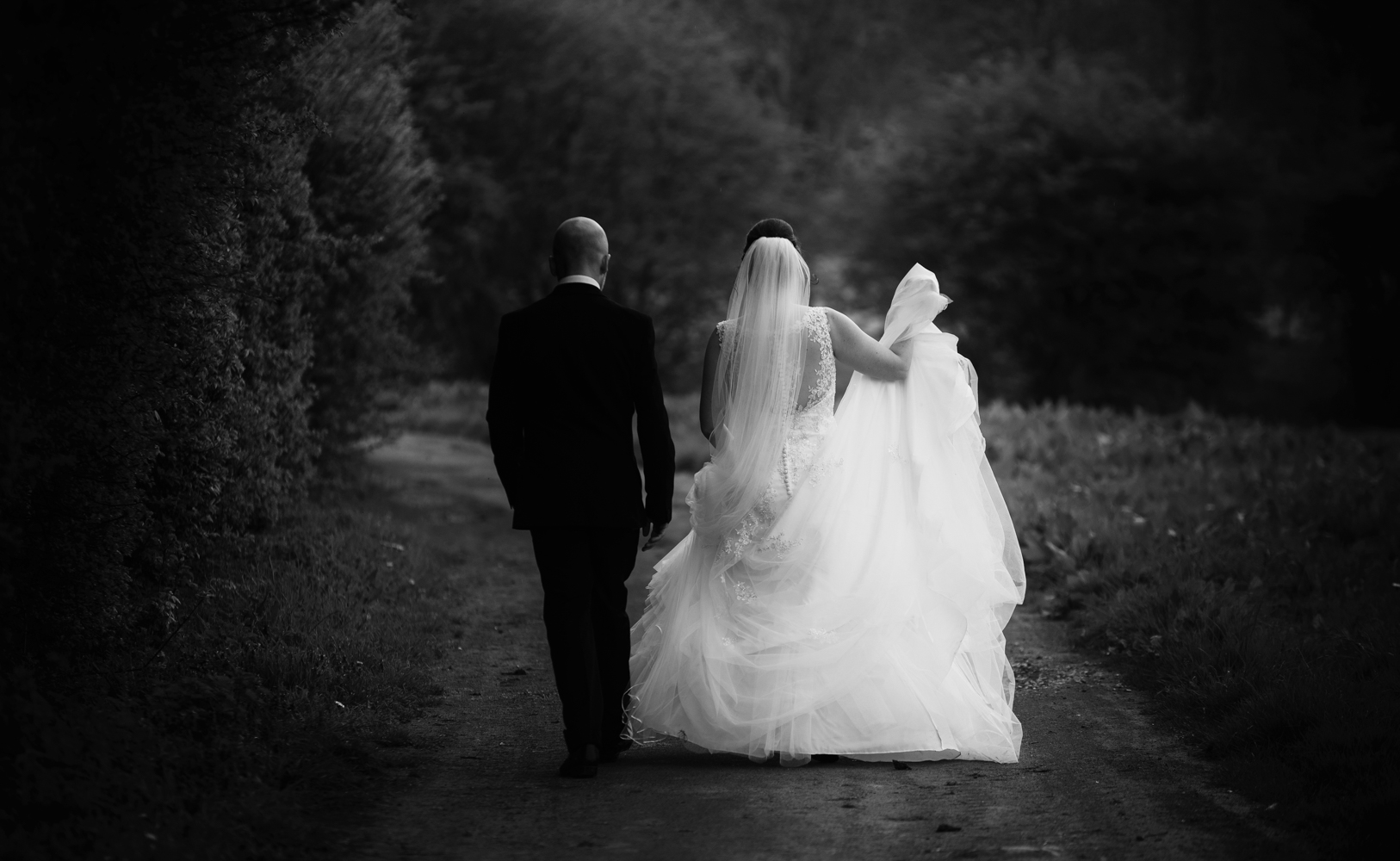 A black and white image of the bride and groom walking away from the camera.jpg