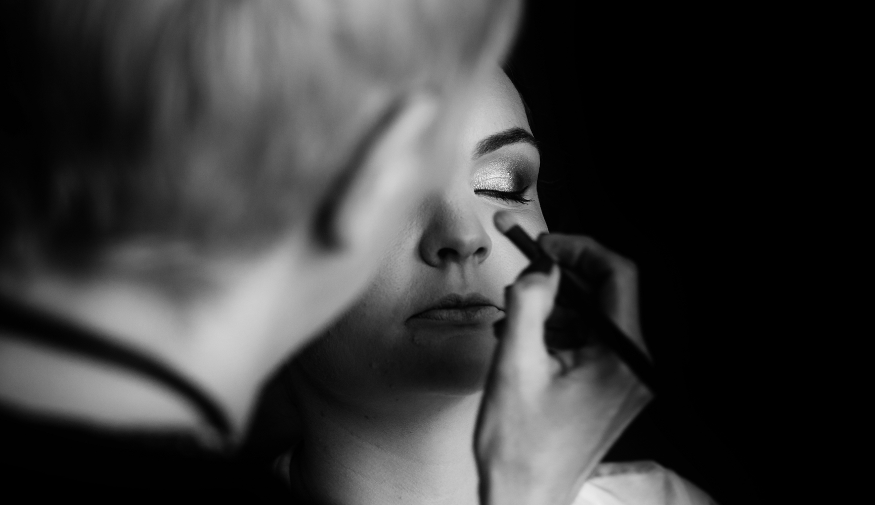 A black and white image of the bride having her eye makeup applied