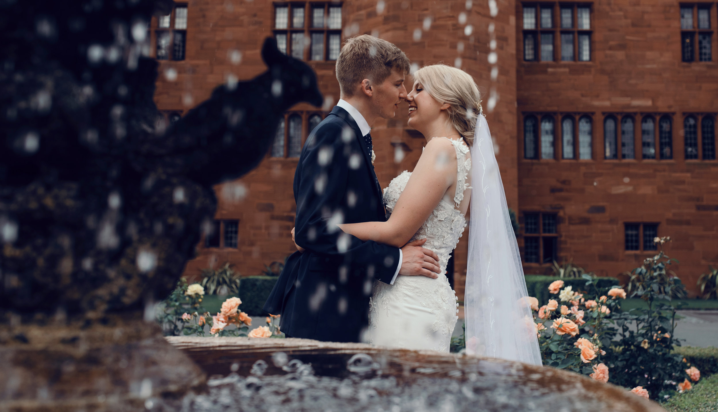 A bride and groom in front of a fountain at Abbey House Hotel