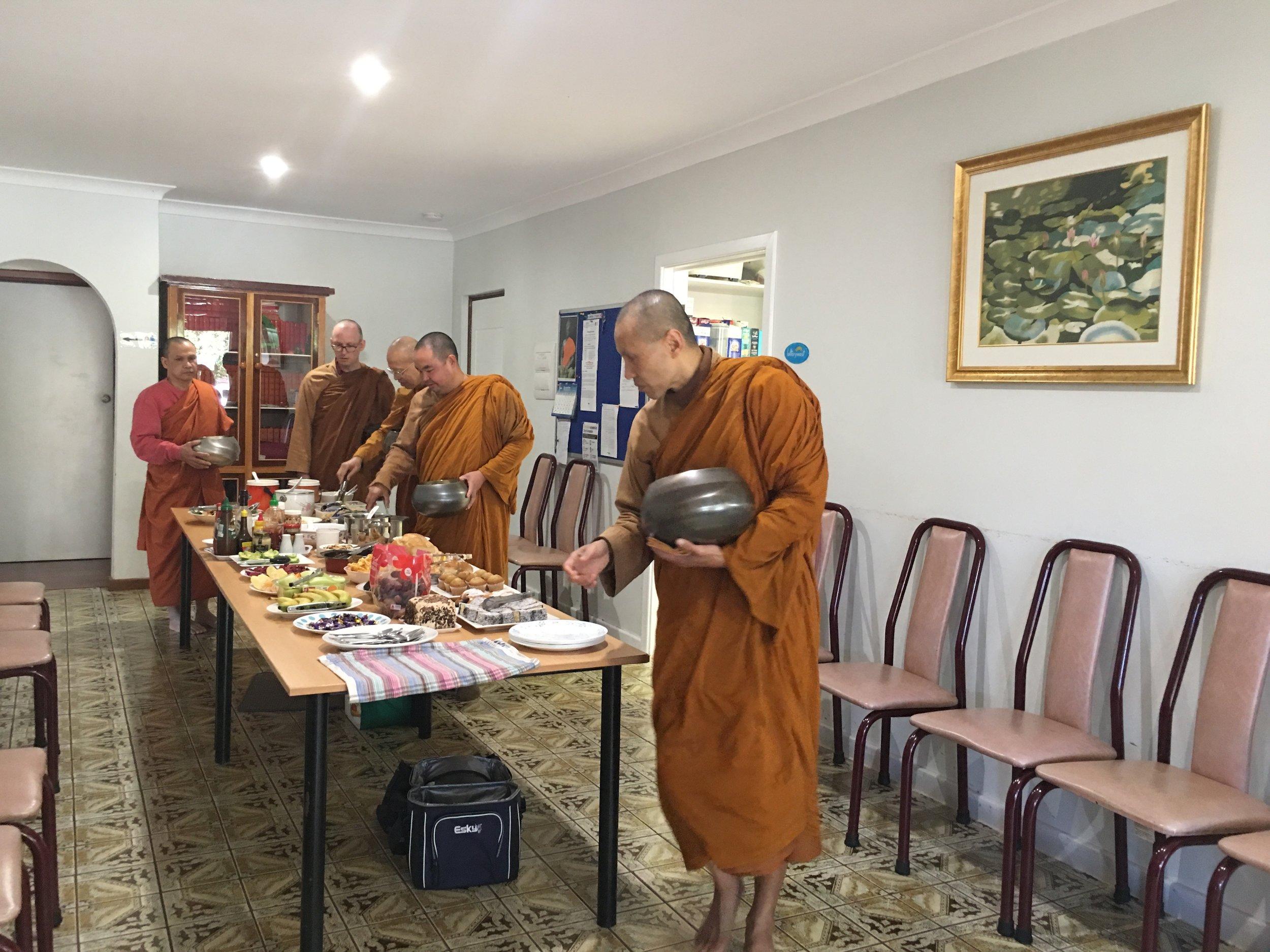 Monks taking dana in the Dining Room.