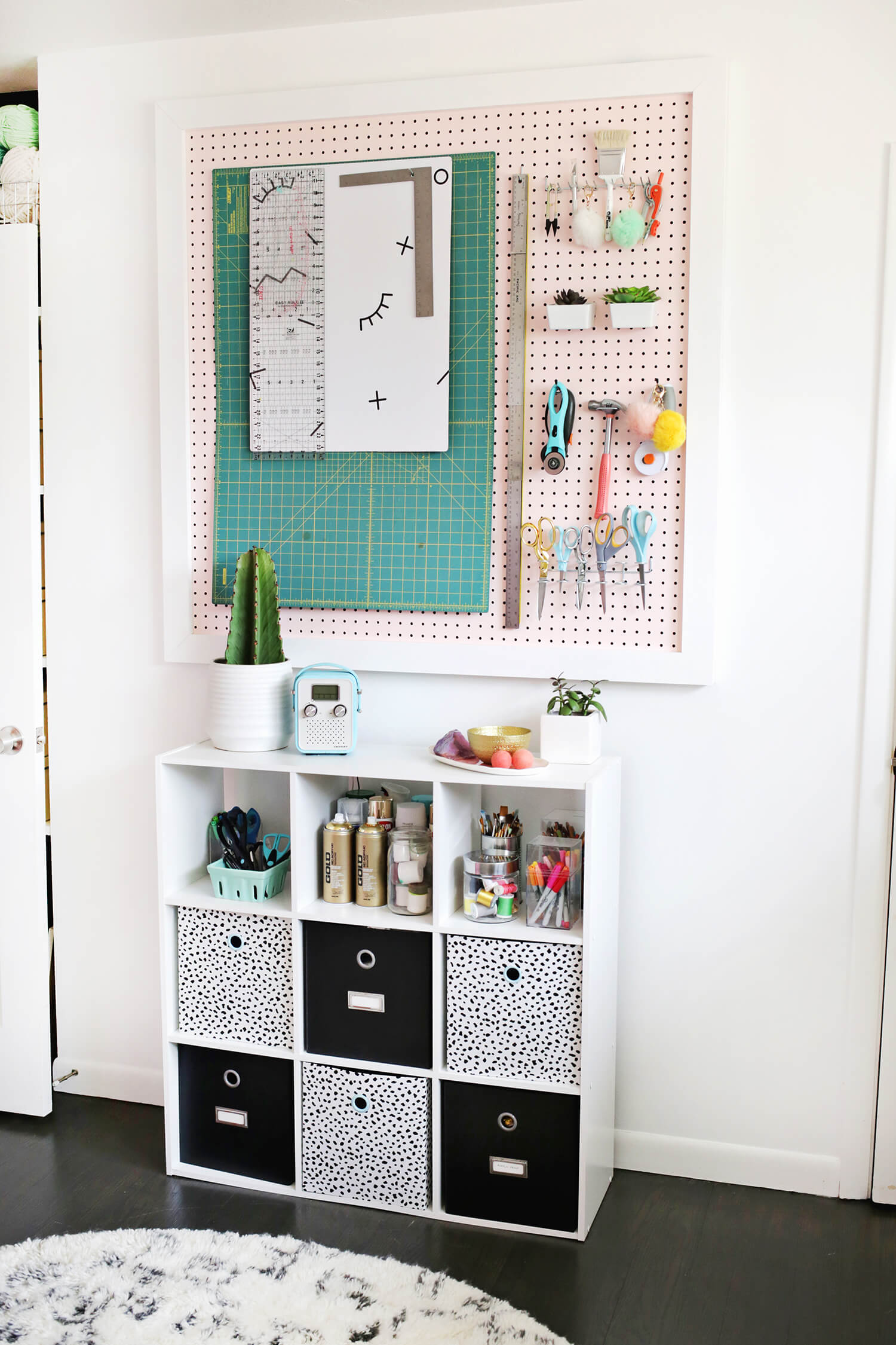 Laura's Craft Room from A Beautiful Mess  - Opposite the pink lockers is a square storage piece that has part closed, part open storage (remember about displaying your favorite pieces) plus a pegboard to hold awkward stuff + cute stuff. PomPoms = necessary crafting equipment.