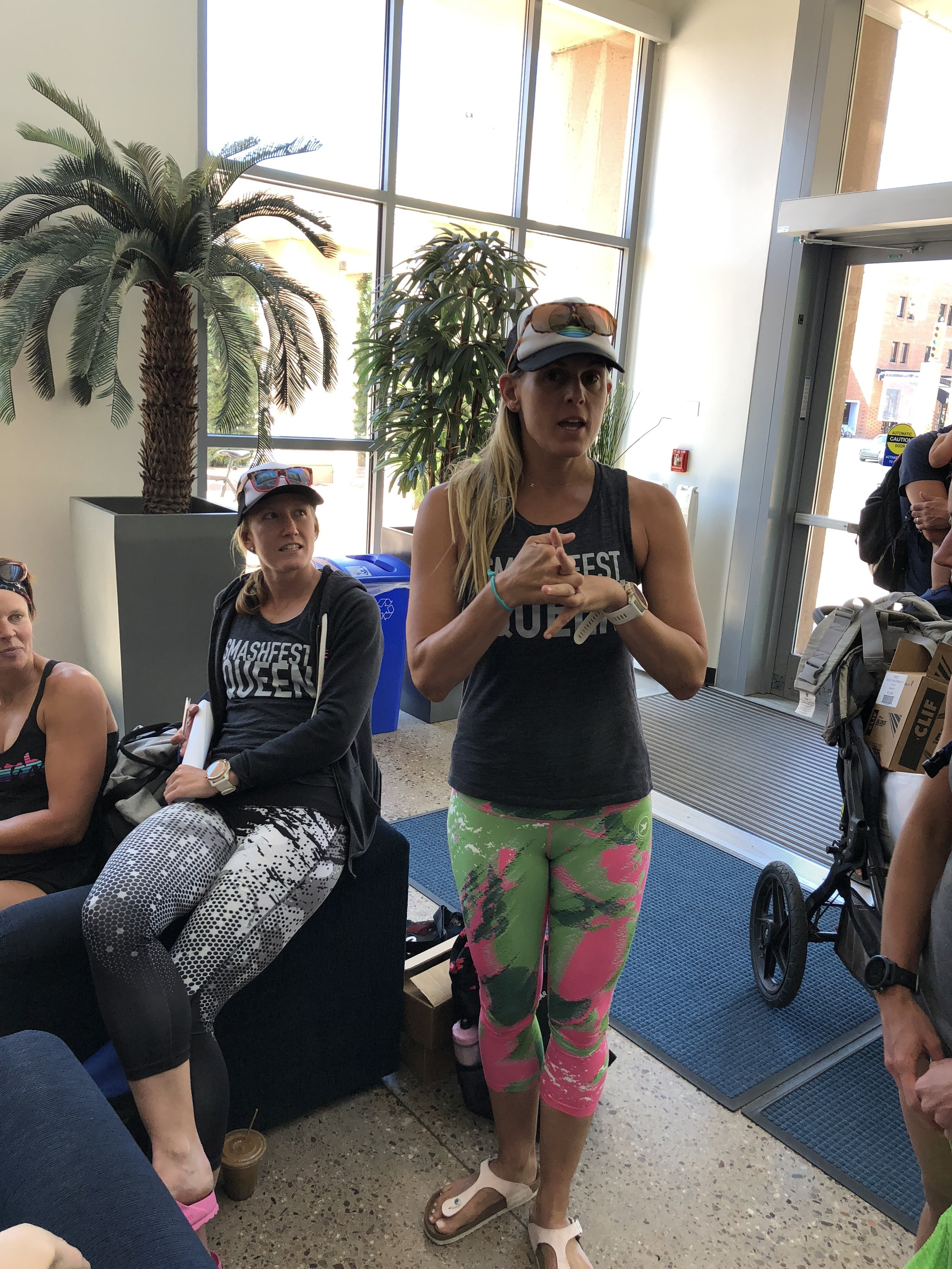 My coach Hillary Biscay, (standing), giving us the camp kick-off speech before our first workout on Thursday afternoon, a 10,000 yard swim, alongside our other coach, Alyssa Godesky, (seated).