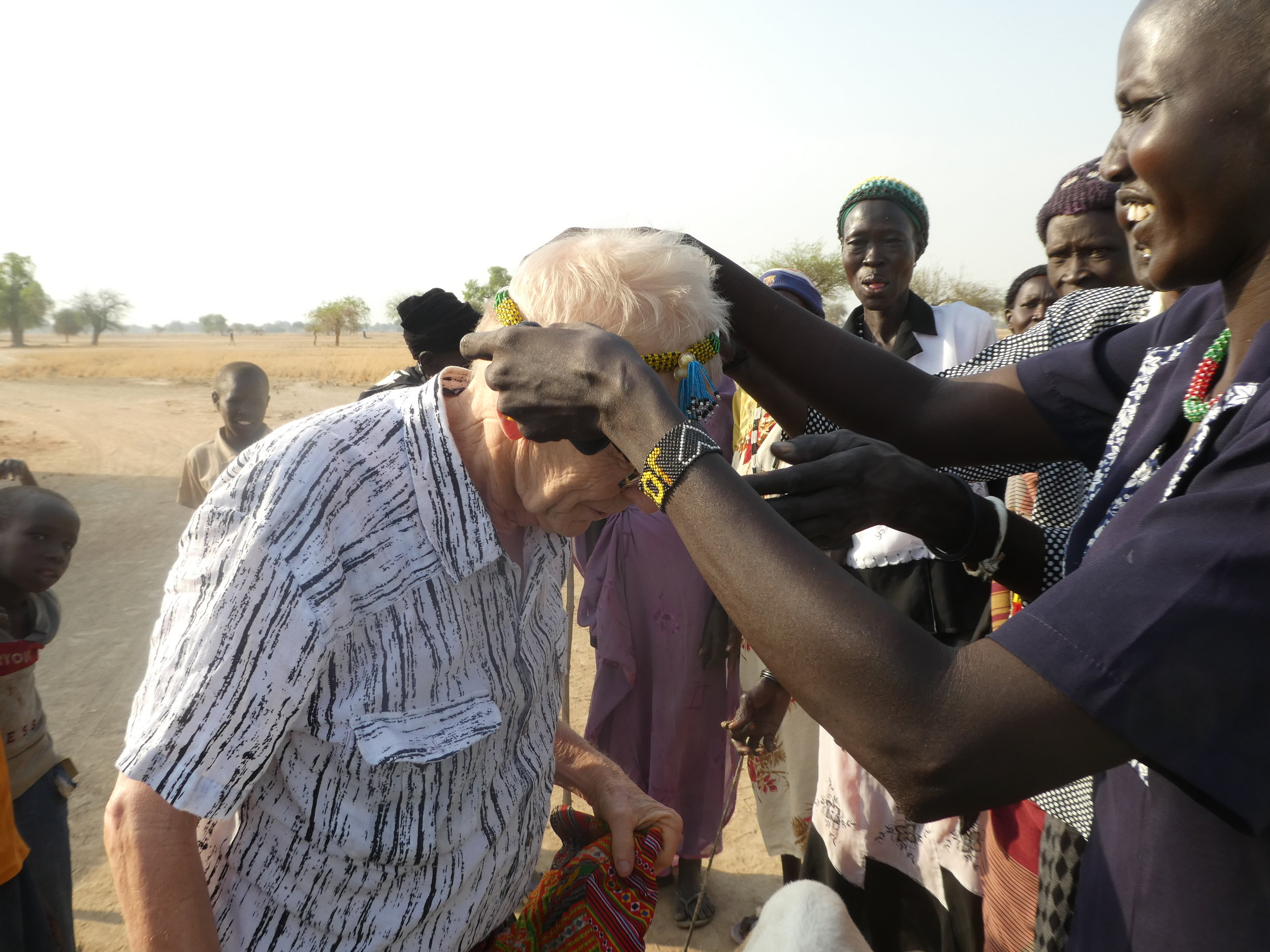 Bill receiving a beaded necklace from one of the mothers whose daughter will be attending school in South Sudan.