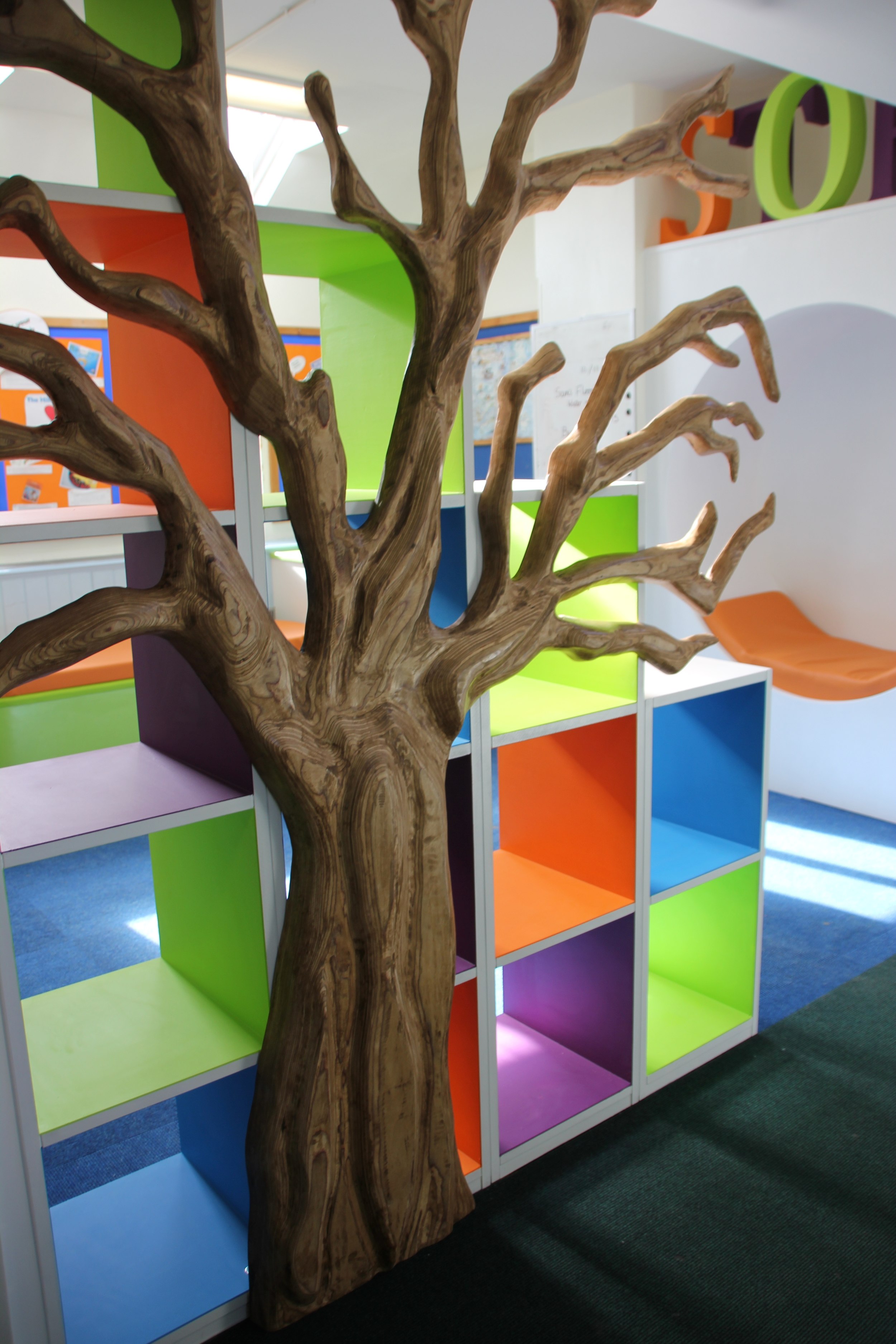 Carved plywood tree and open box shelving