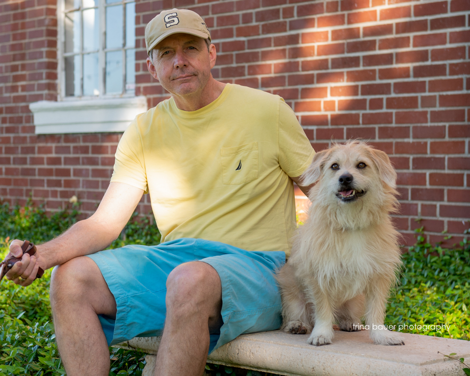 man and dog on bench in front of house