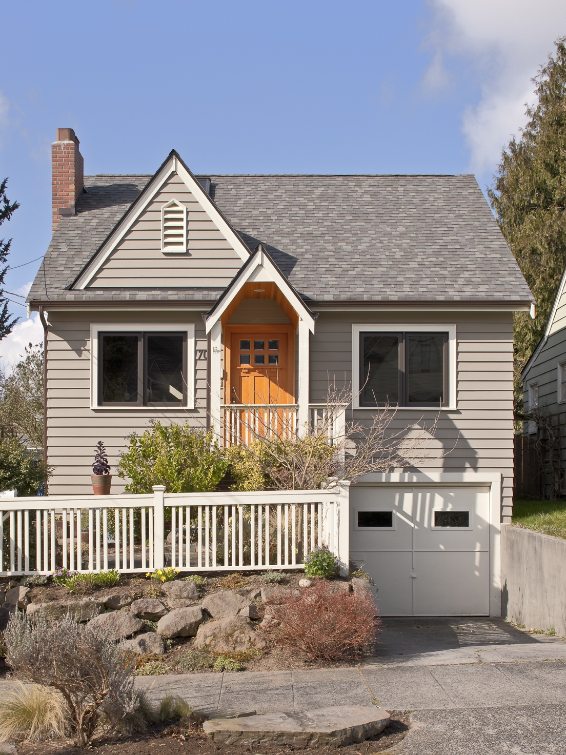 Seattle Craftsman addition with quaint front entry porch, white picket fence and white garage door