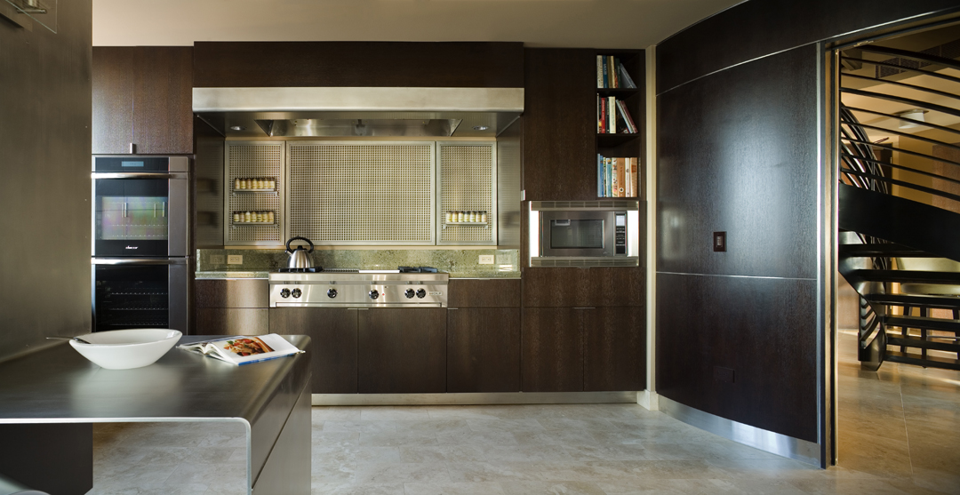 Contemporary Seattle Kitchen Design showing stained oak cabinets, a custom folded steel plate counter, and a beautiful range