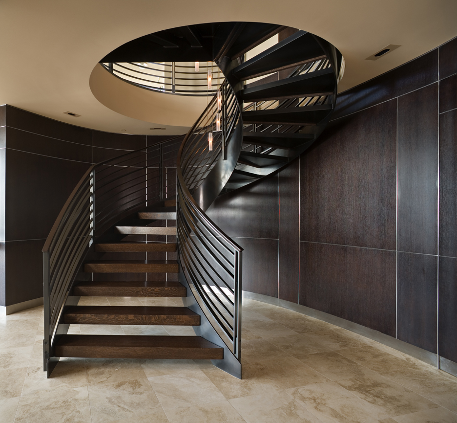 Seattle spiral stair, curved wood walls with hidden doors beyond, travertine floor