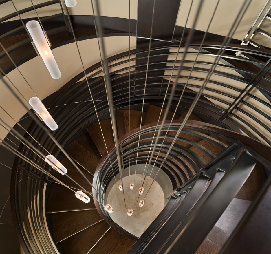 amazing spiral staircase with custom metal guardrail, stained wood treads, and spiral glass and steel chandelier