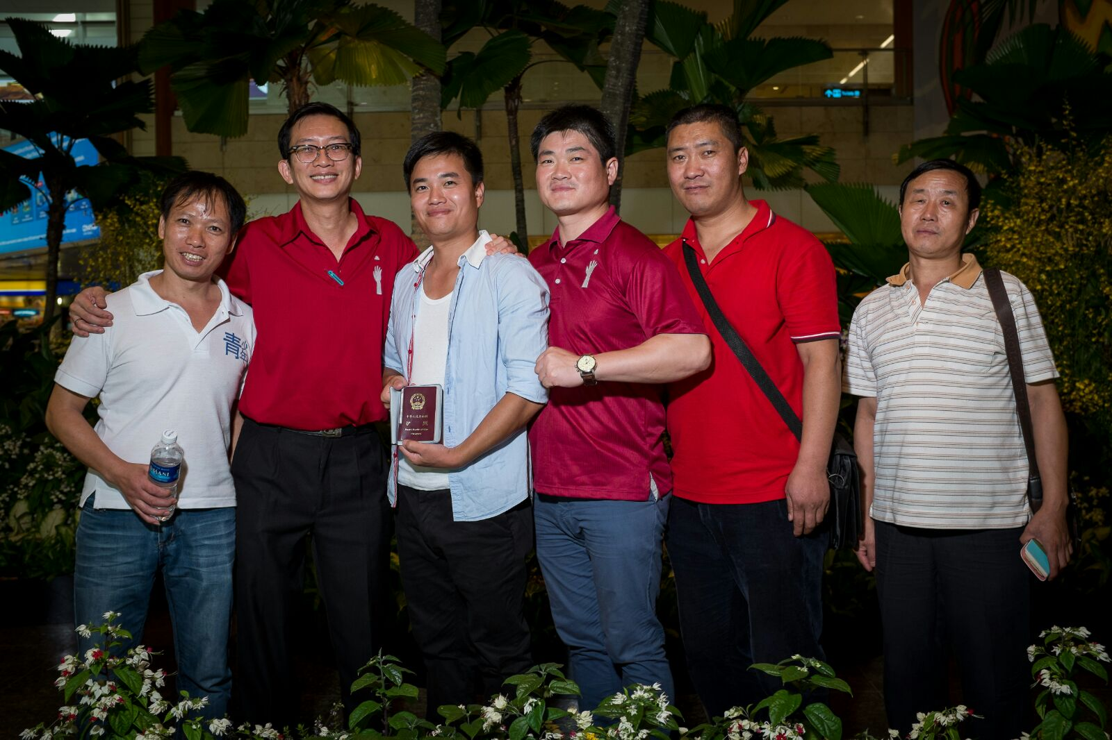 ZHang at Changi Airport being sent off by our case manager, Jeff, and his migrant worker friends.