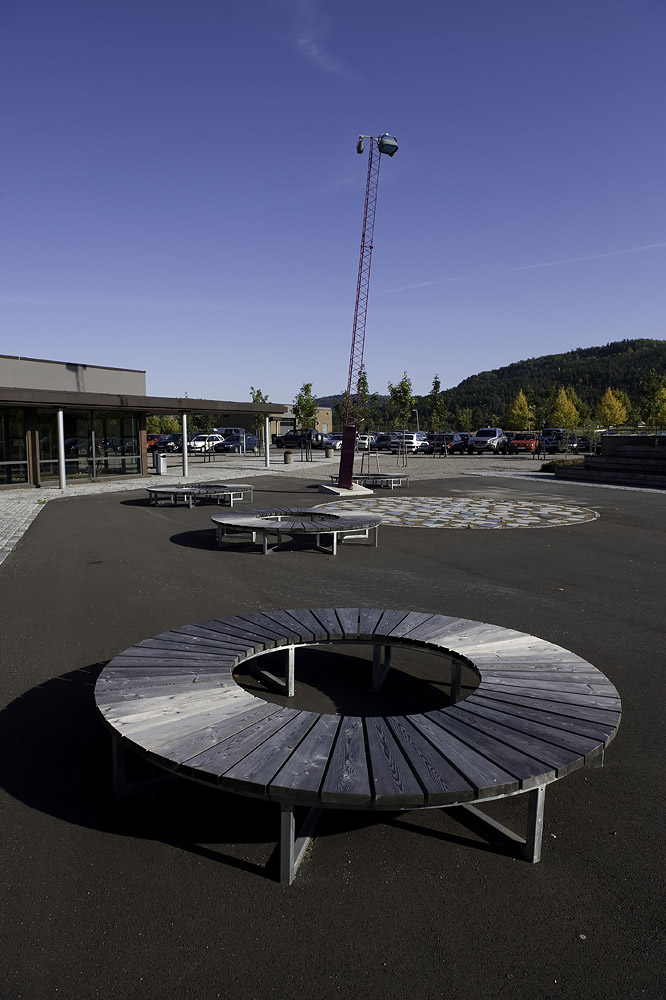 Spesialtegnede runde benker og utsmykking på grusplassen foran administrasjonsbygget. Foto Dag Jensen.