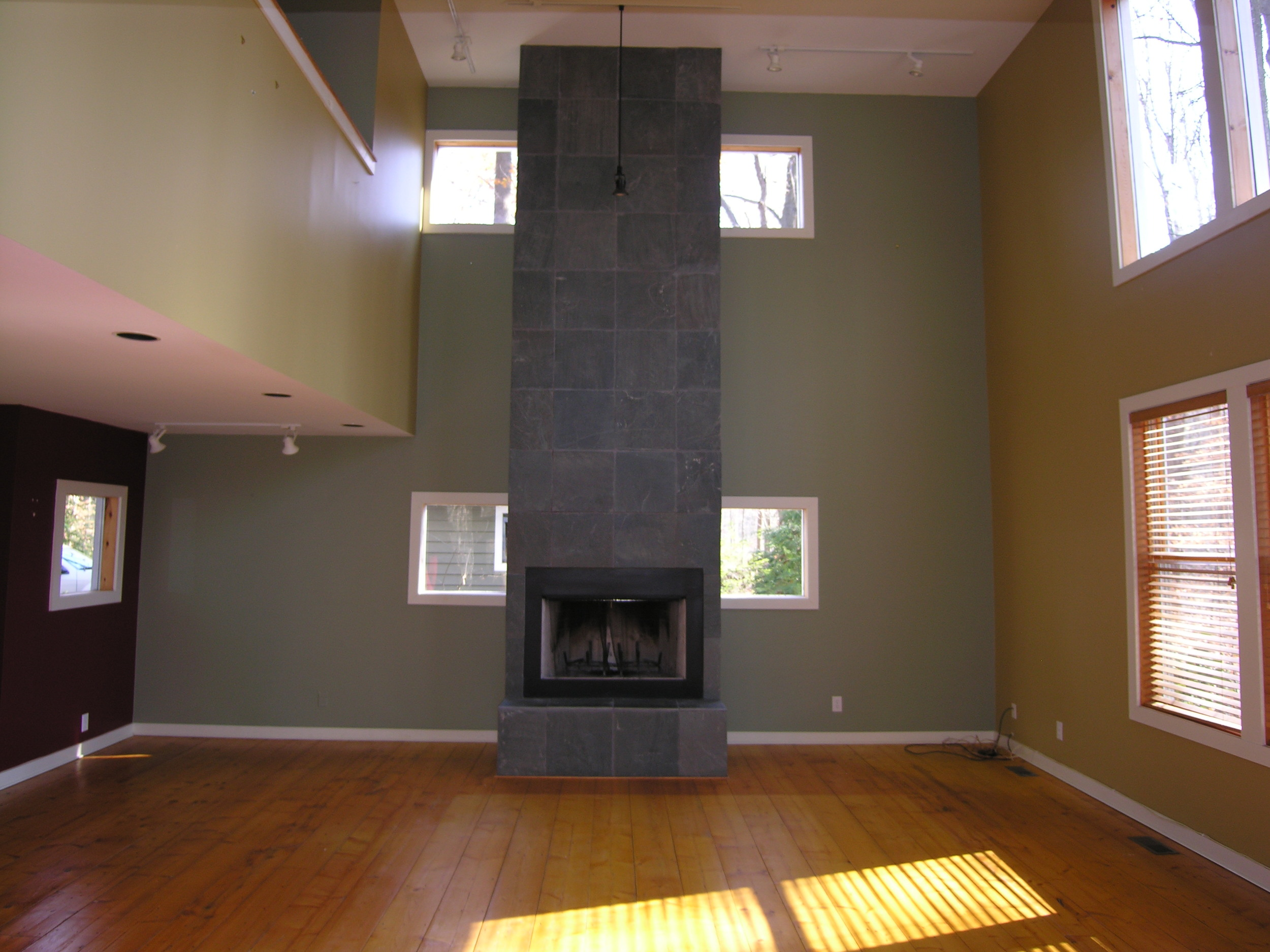 BEFORE: The fireplace soars over 2 stories, but the green walls blend into the slate surround.