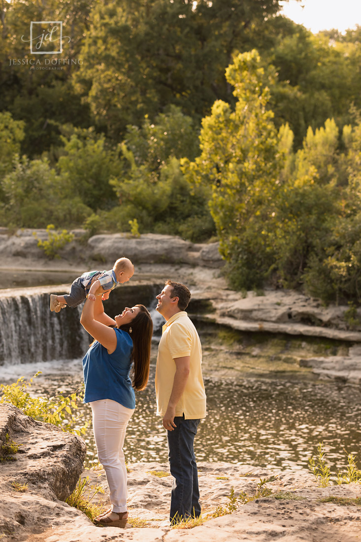 holding baby in front of waterfall at memorial park in roundrock