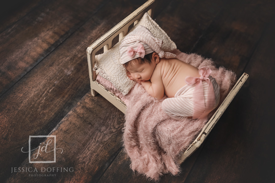 newborn girl sleeping pink