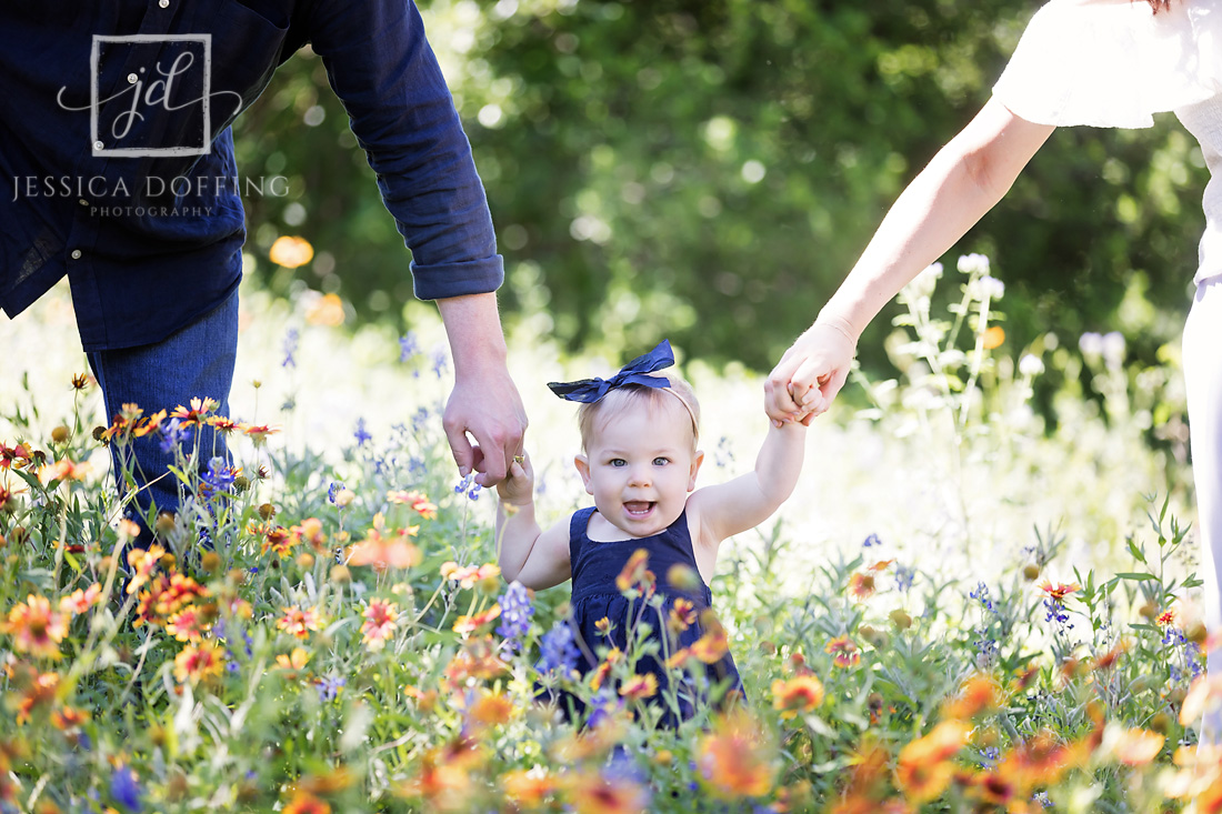 baby girl parents hands wildflowers
