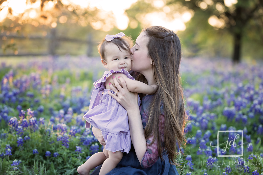 mom kissing daughter bluebonnets