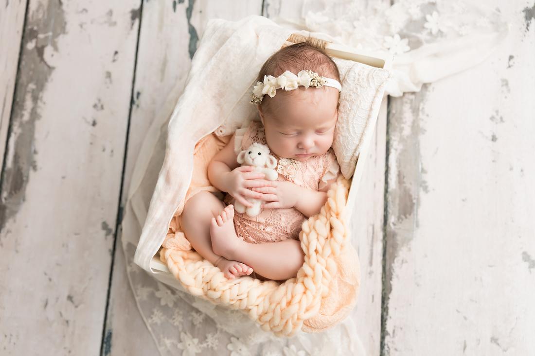 newborn girl in peach with lamb stuffie