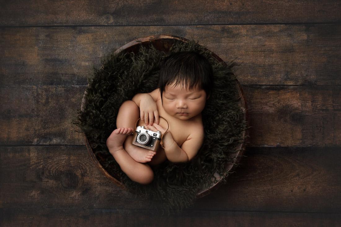newborn boy with camera in bowl prop