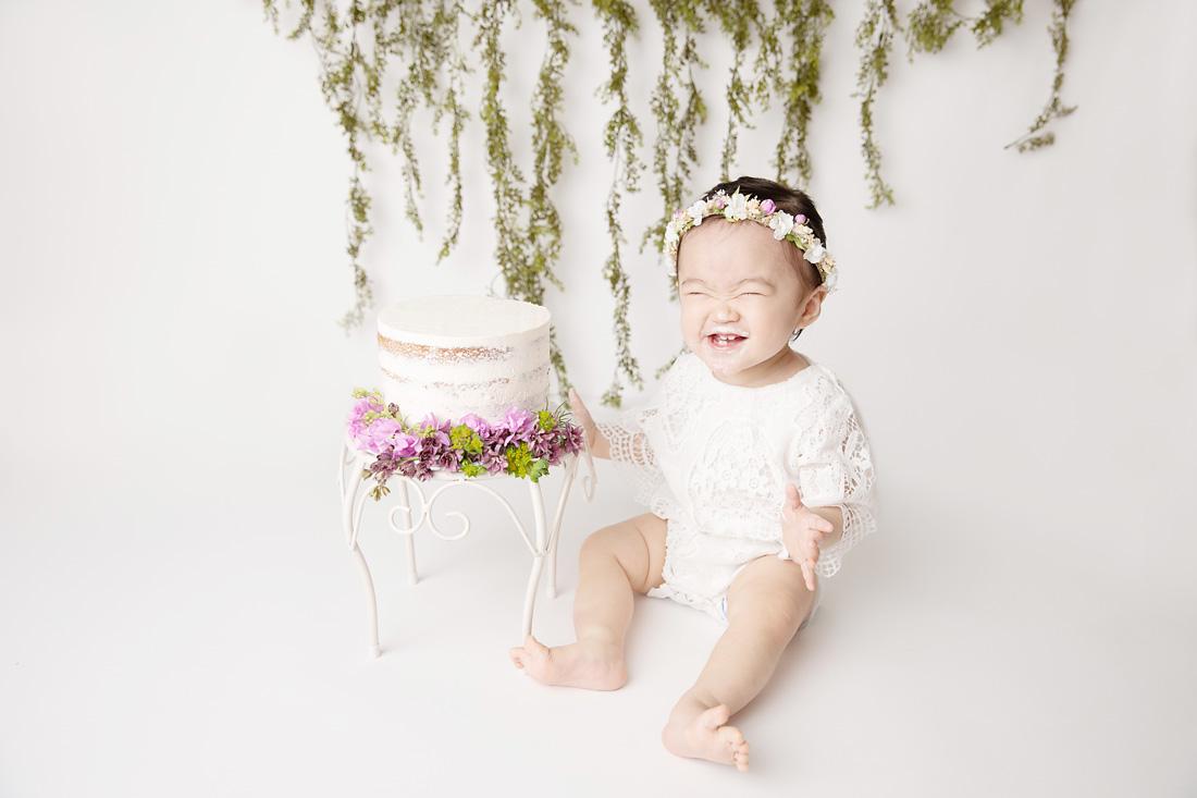 girl cake smash flowers with big smile