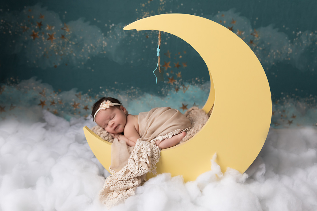 girl newborn on moon prop