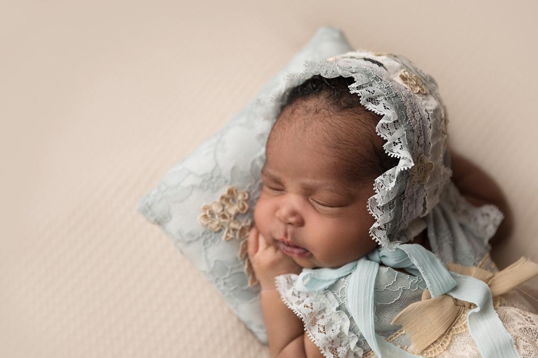 newborn girl in blue bonnet on pillow
