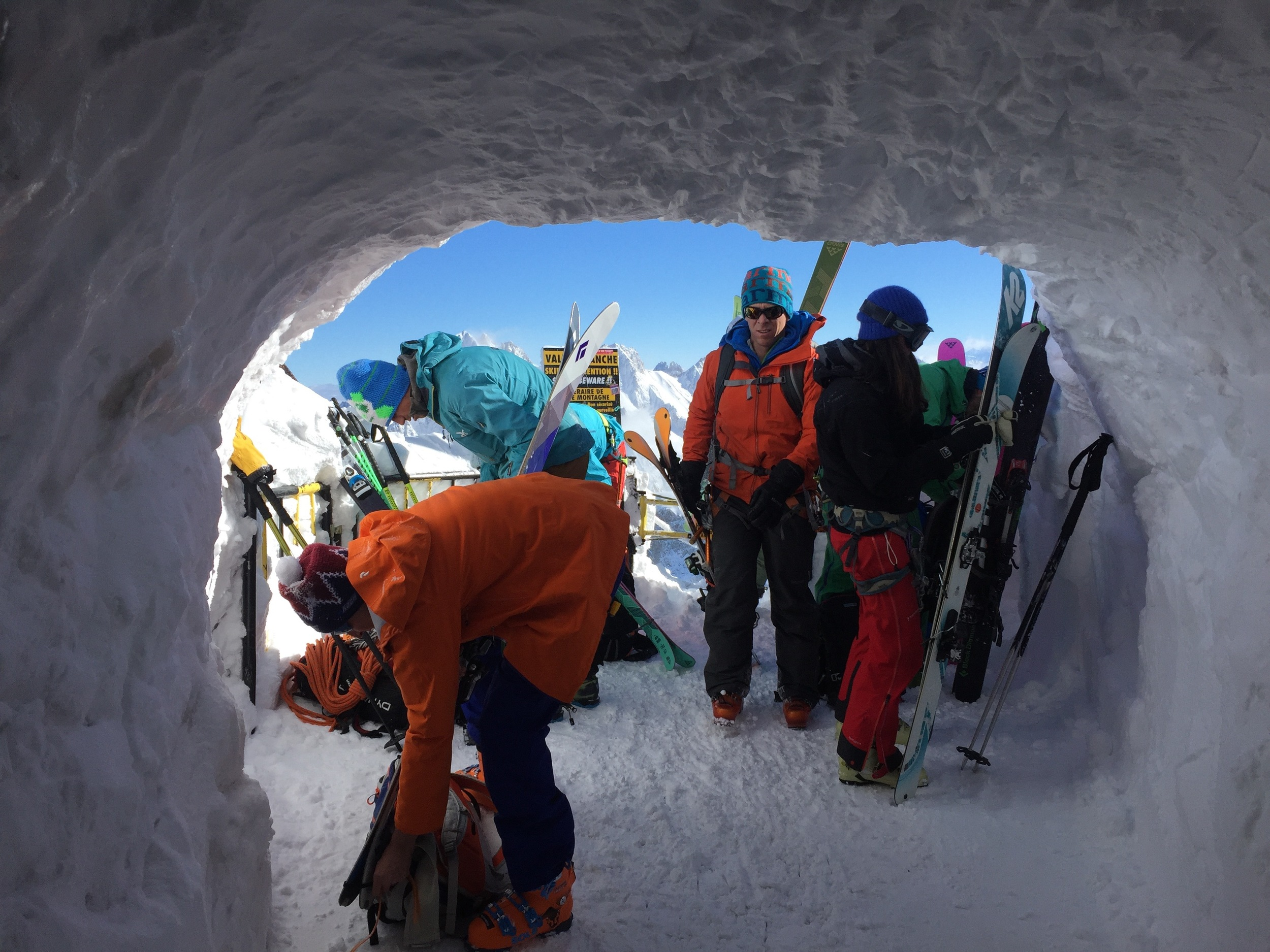 Skiers emerge from the ice tunnel and scramble to secure gear to their packs before making the trek on the arête