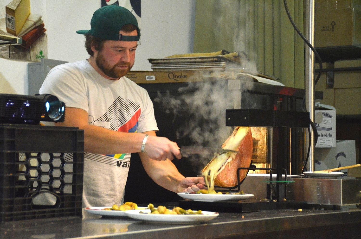 Tripp scrapes a layer of melted cheese on top of the potatoes to make a plate of raclette