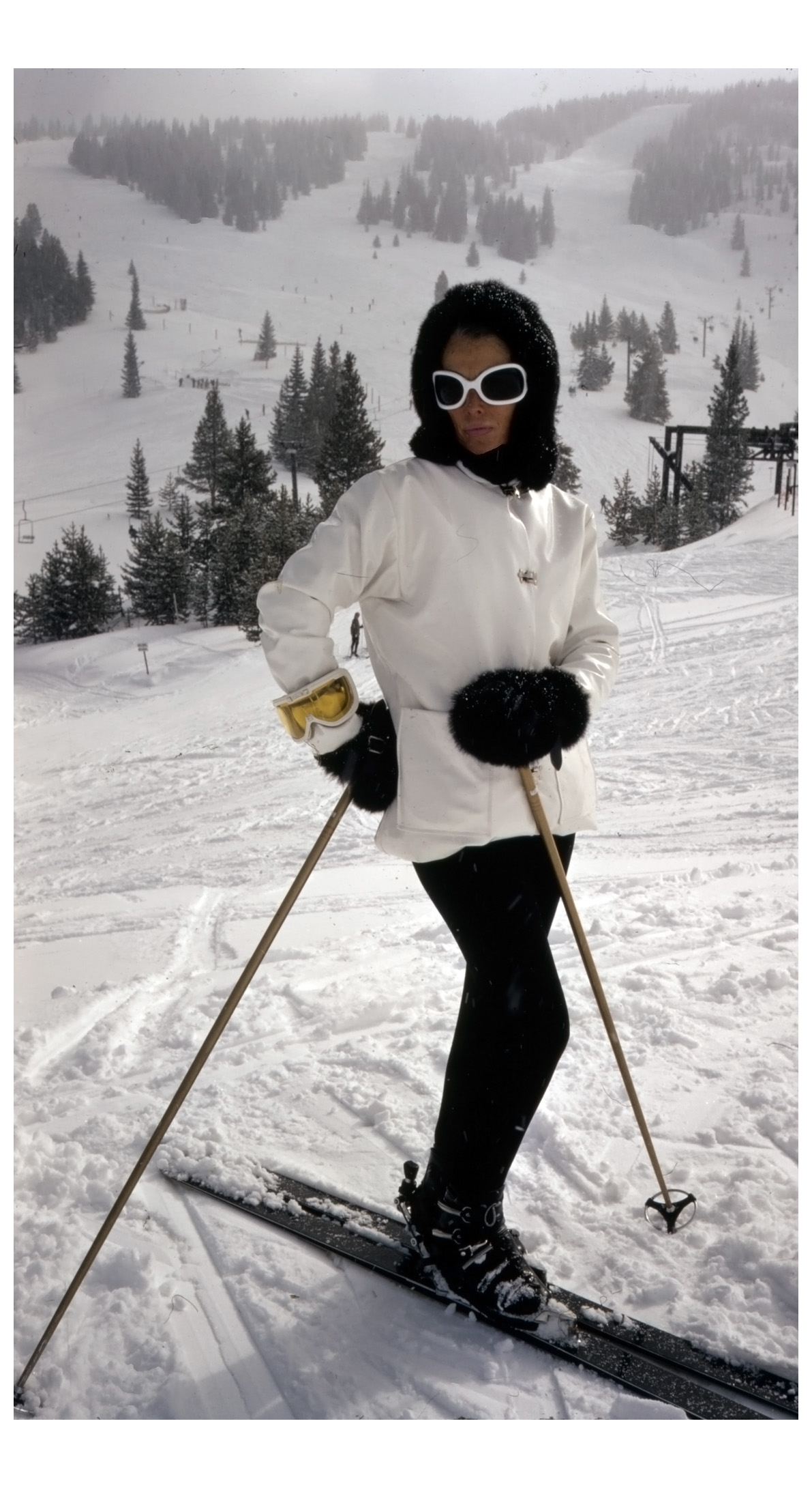 ann-bonfoey-taylor-full-length-portrait-wearing-a-ski-outfit-including-a-white-vinyl-jacket-black-pants-and-a-black-rabbit-hood-vail-colorado-1967.jpg