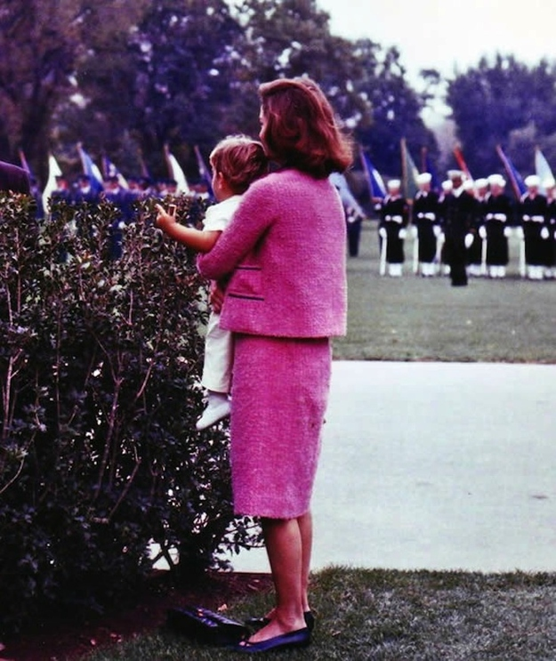 Jackie Kennedy wearing her iconic pink suit holding John Jr. as she awaits the arrival of Prime Minister Ahmed Ben Bella of Algeria (October 1962)