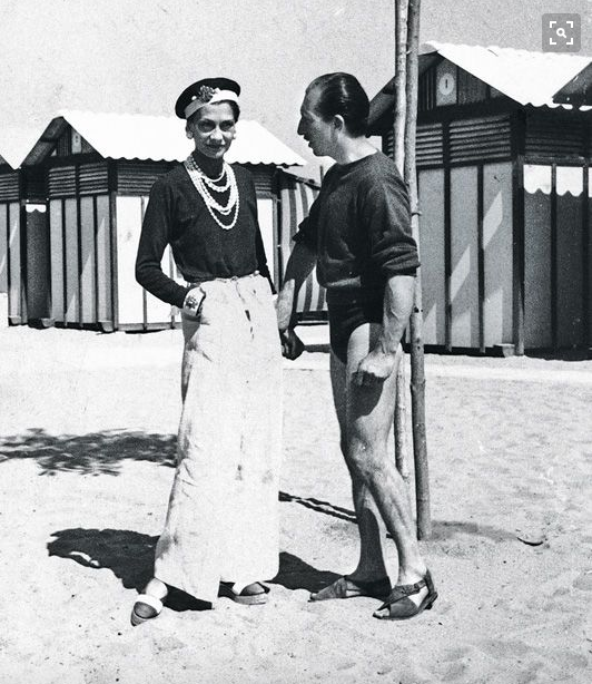 Coco Chanel sporting a sun tan on the beach alongside Duke Laurino of Rome, 1930