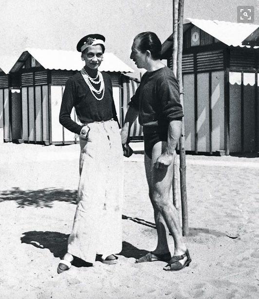 Coco Chanel sporting a sun tan on the beach alongside Duke Laurino of Rome, 1930