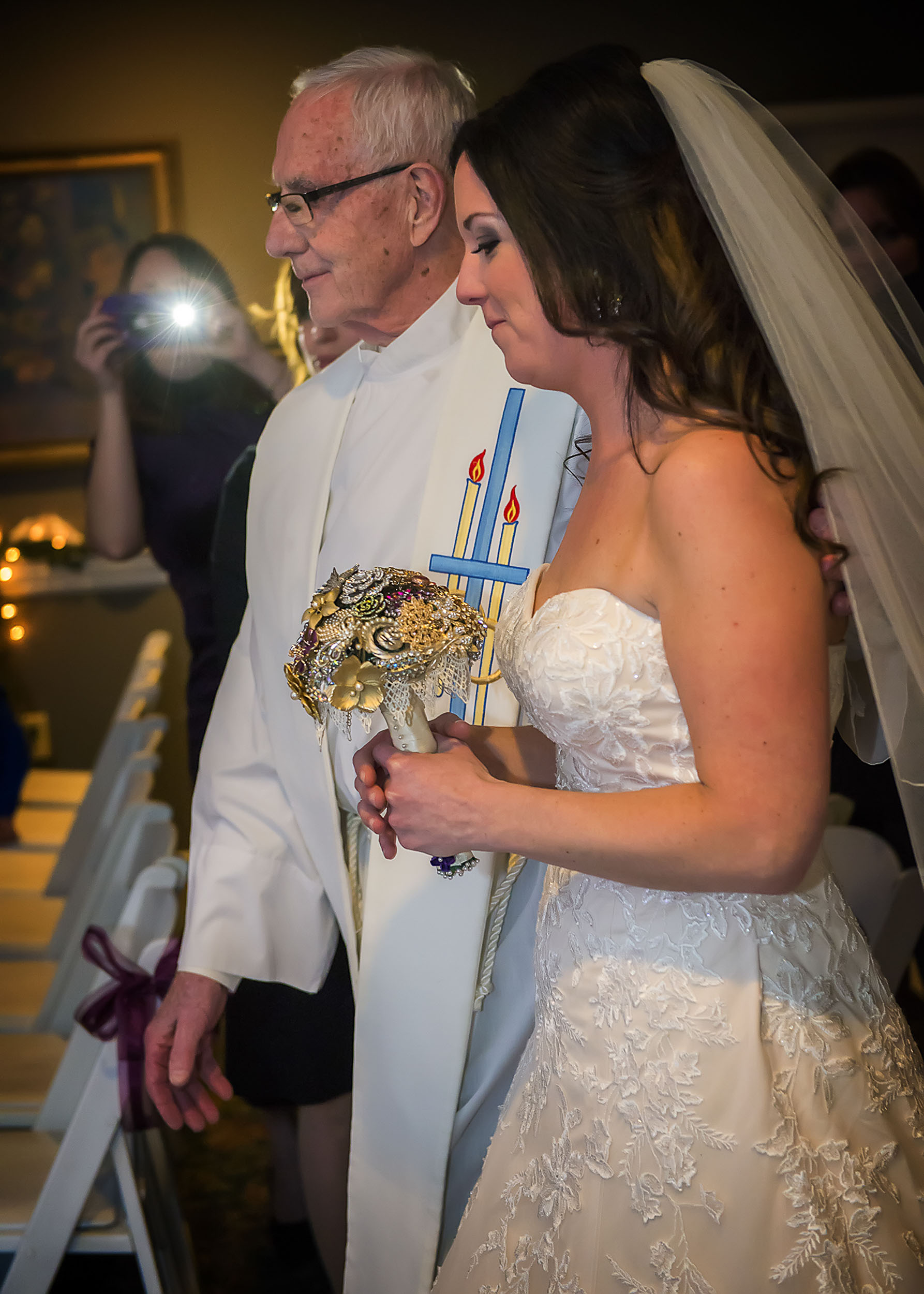 The officiant in this photo is also the bride's father.  I love this moment as he walks her down the aisle to perform the ceremony, but unfortunately, the moment is ruined by the distracting flash in the background.