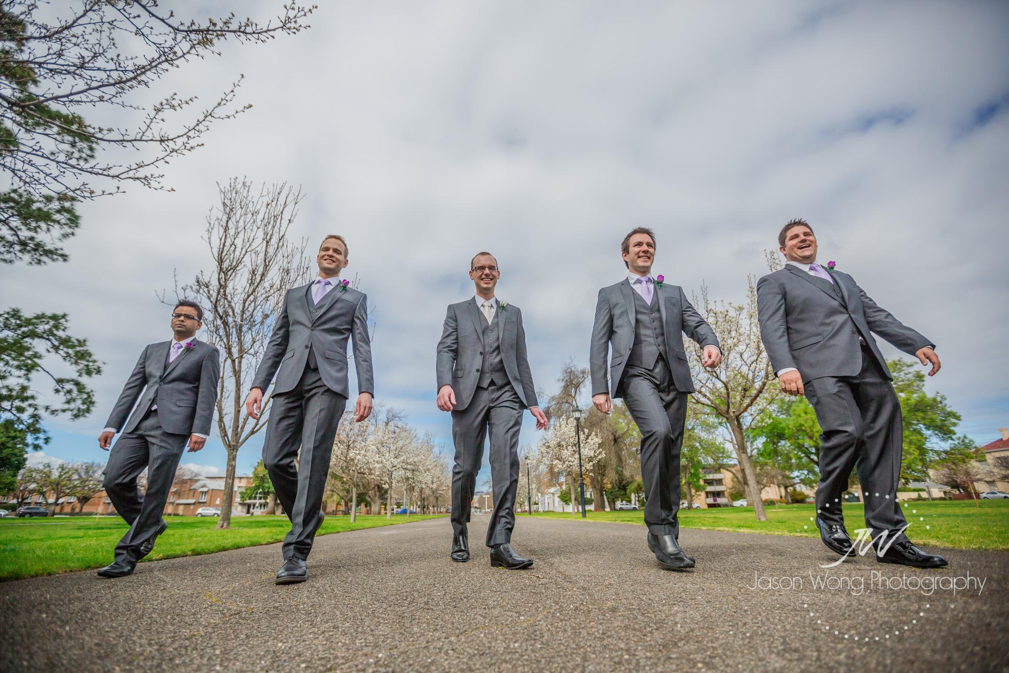 groom-and-groomsmen-walk-in-garden.jpg