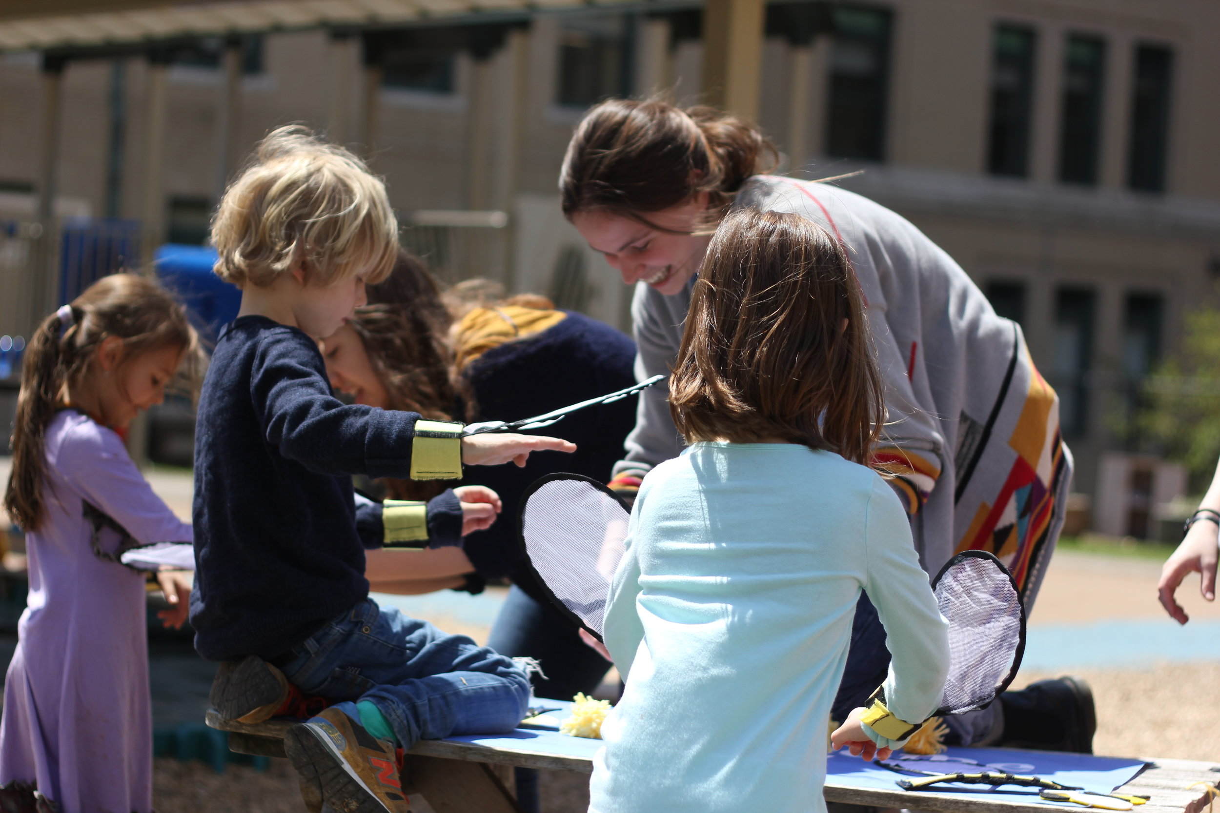 """After giving a brief introduction about bees and pollination, the kids dressed up in the wearable bee wings in preparation for collecting and distributing """"pollen"""" to the flowers."""