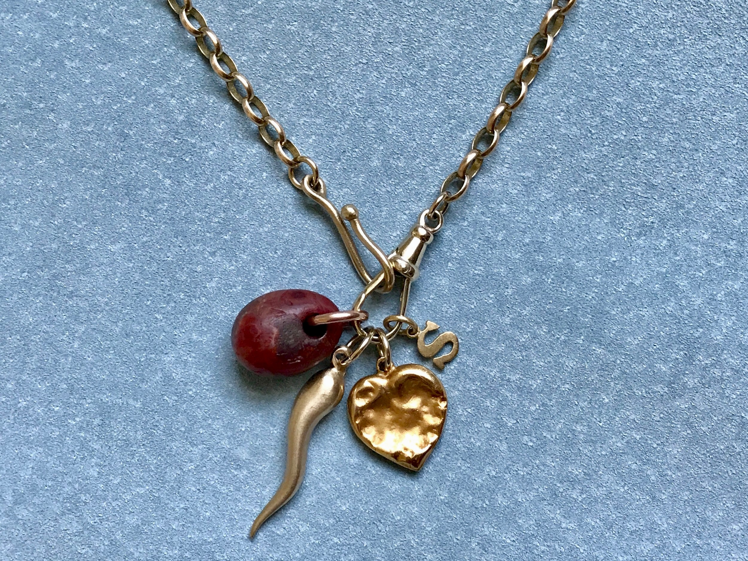 YELLOW BELCHER CHAIN WITH NEOLITHIC CARNELIAN, ITALIAN HORN, CHEWED HEART AND LETTER CHARM