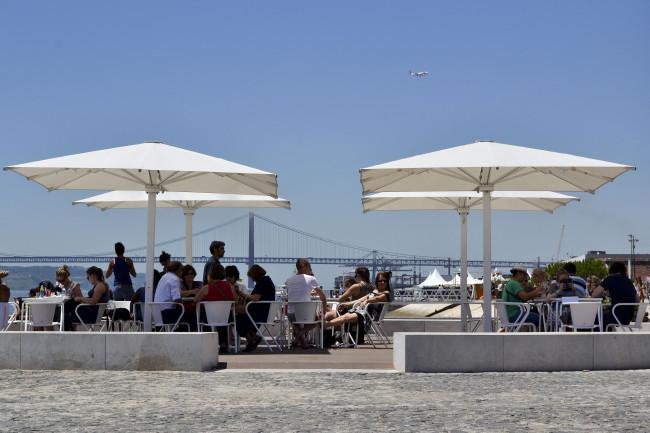 Turistas sentados numa esplanada usufruem da nova zona ribeirinha da Ribeira das Naus, localizada entre o Terreiro do Paço e o Cais do Sodré, 15 de julho, em Lisboa (Tiago Marques/ Lusa)