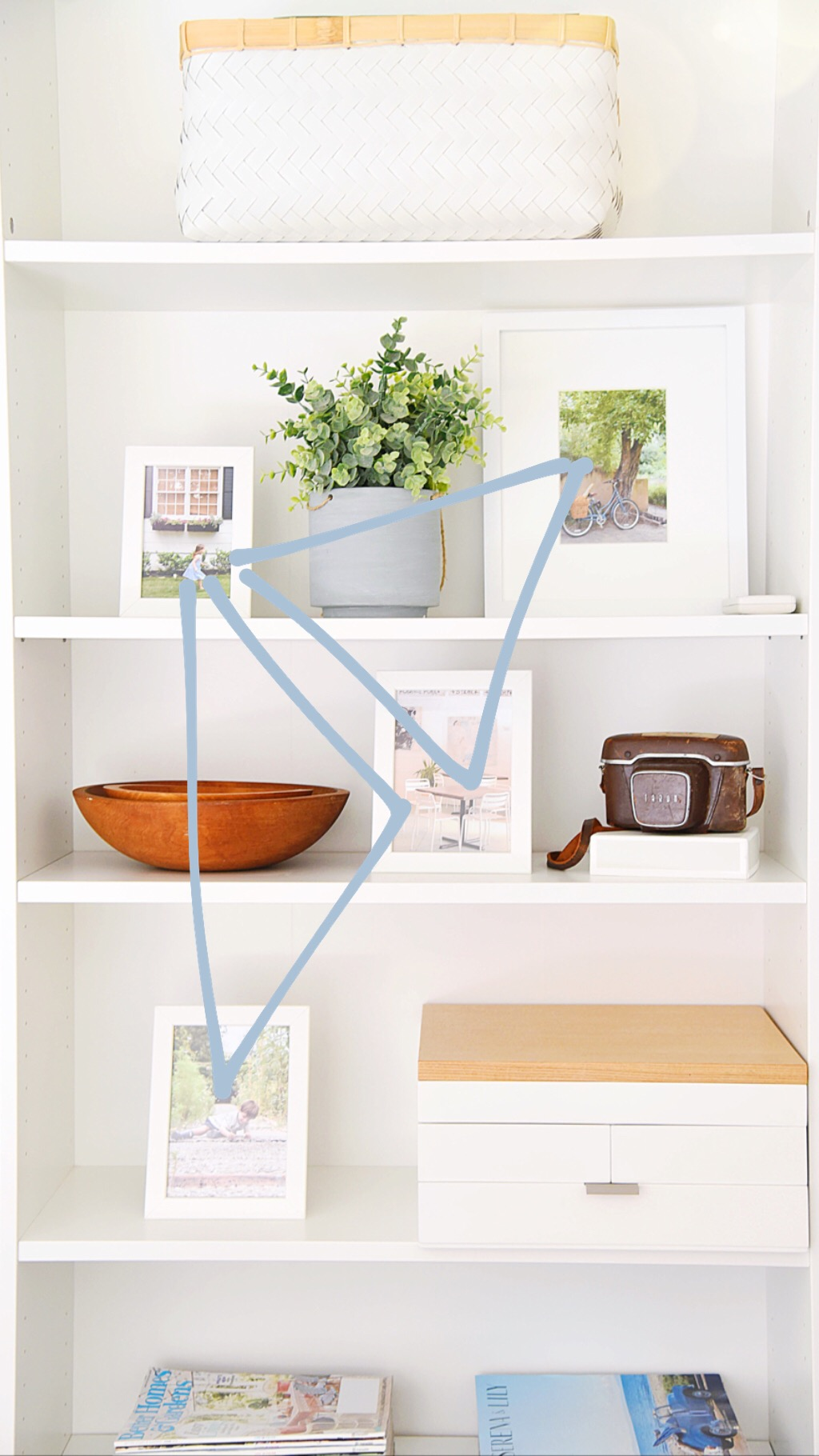 "- This concept is taken a step further for these like items. By using overlapping triangles (what then can turn into ""V"" or ""Z"" patterns as well), a group of picture frames is evenly distributed on a shelf in a way that looks effortless, but rather was very intentional :)"