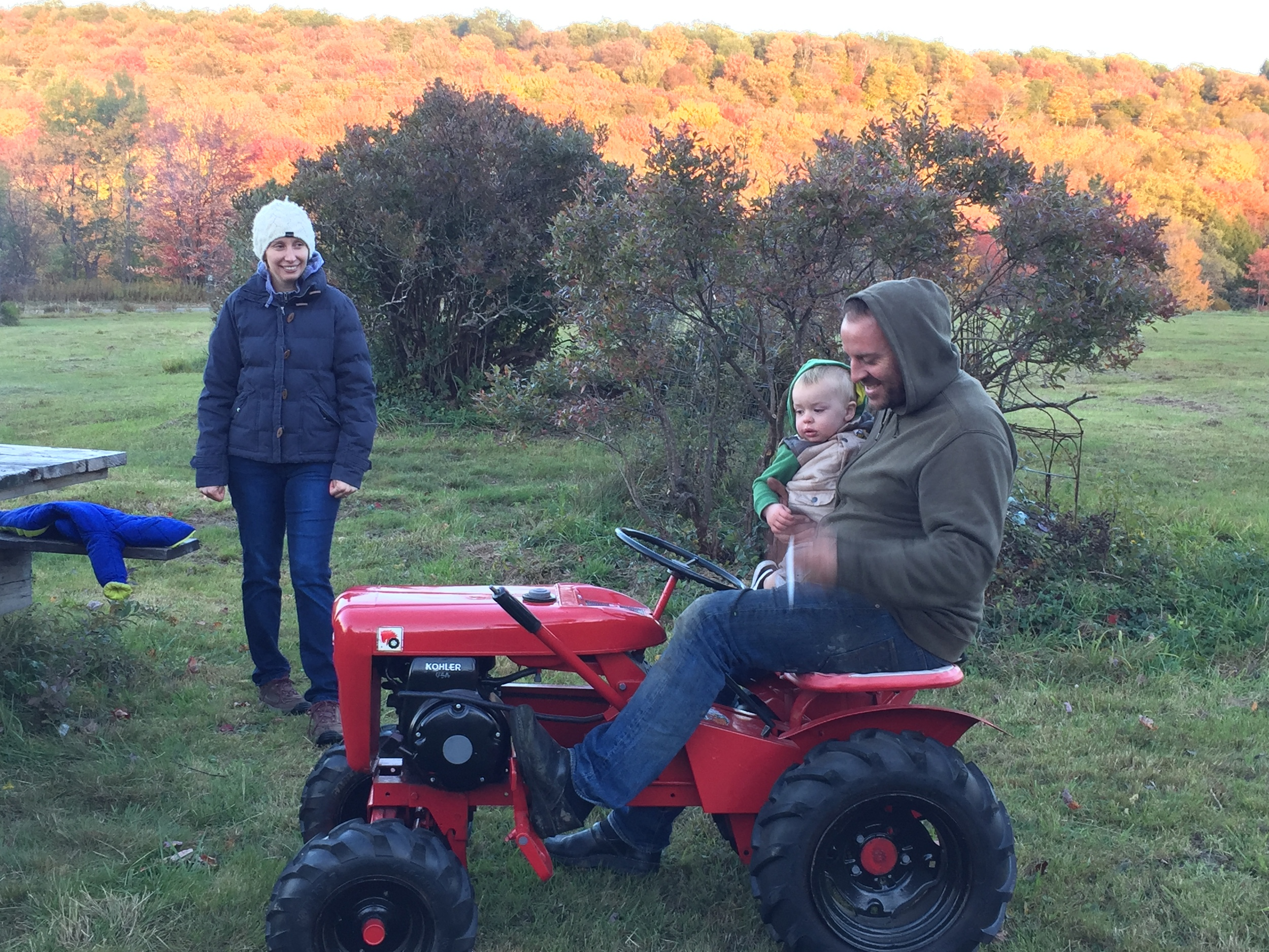 Kristin, Josh and Rowan, their 18-month son, who loves riding on the many tractors they've got on their property.