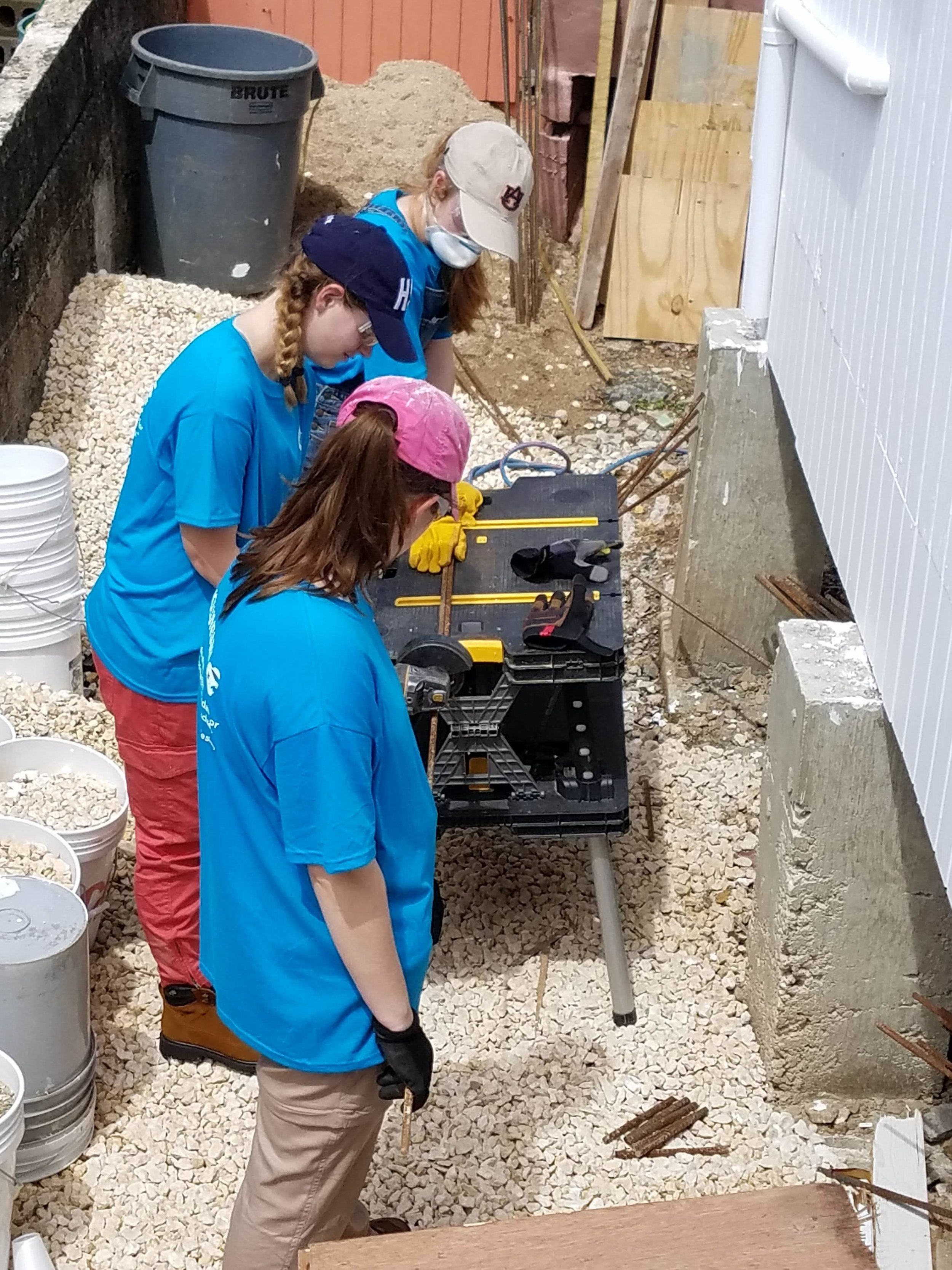 Bekah Wommack, Megan Kucera, and Sarah Jane Thompsonfrom Team 3 are shown cutting rebar. They spent most of the day sorting wood, rebarring, and doing a wide variety of other things.