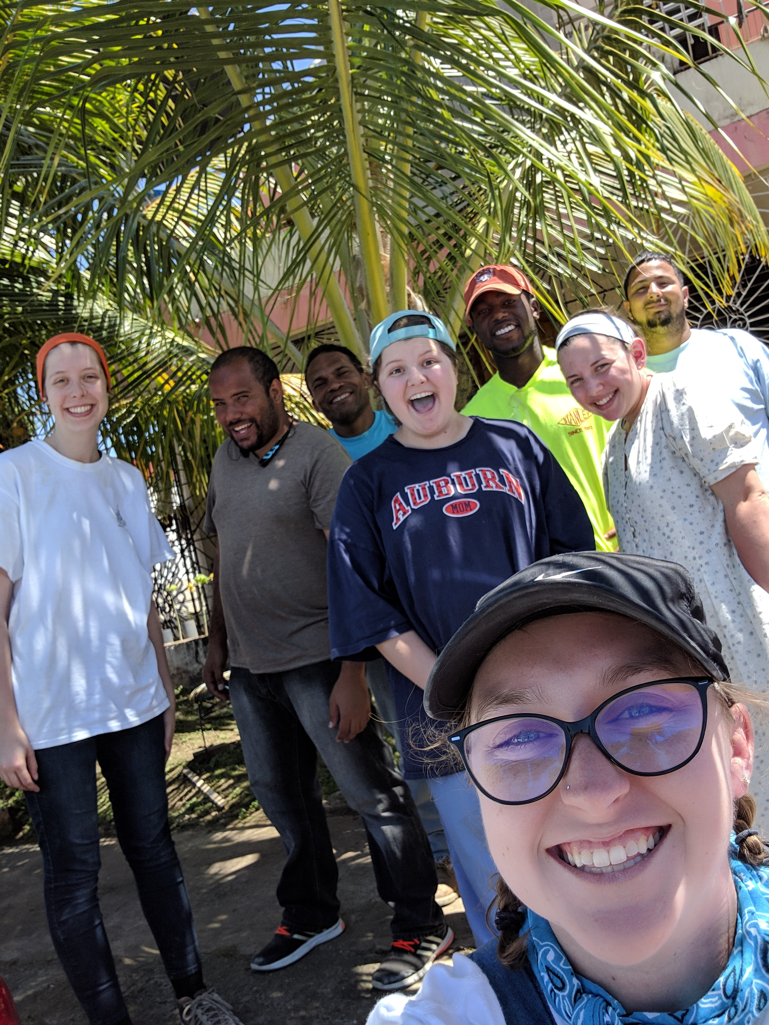 An excited Team 2/ Agua de Coco smiles under a palm tree as they finish up the week's work