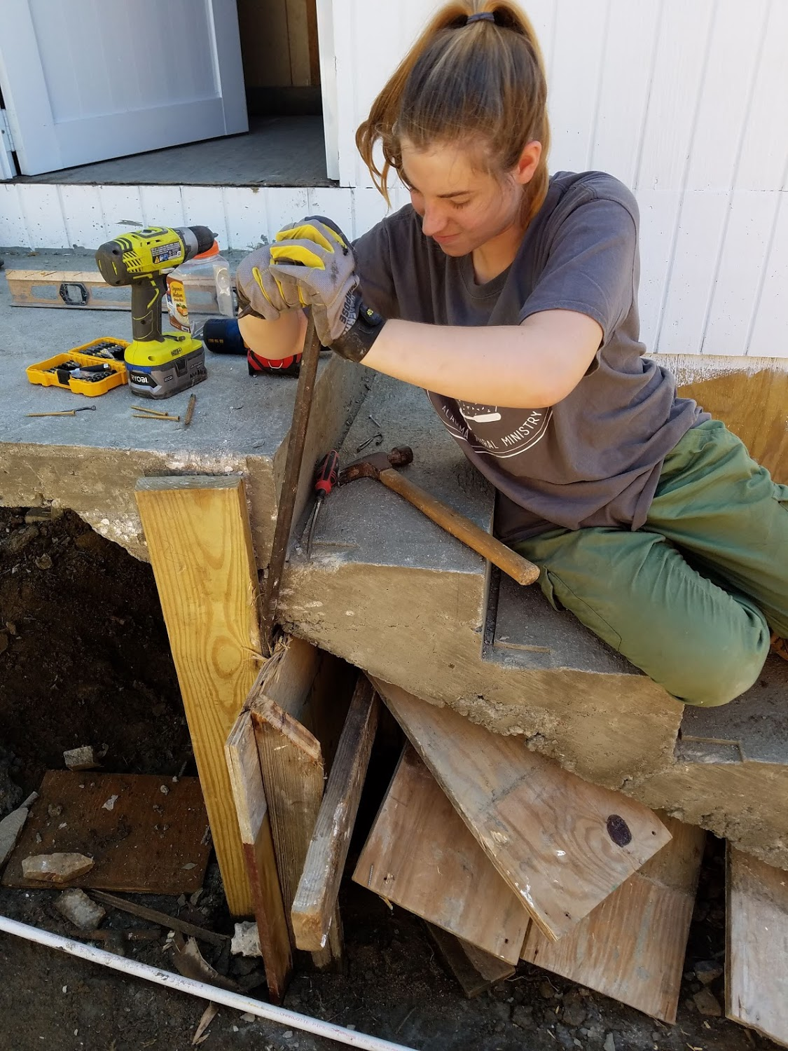 Megan Kucera tries to tear away some old wood from under the stairs