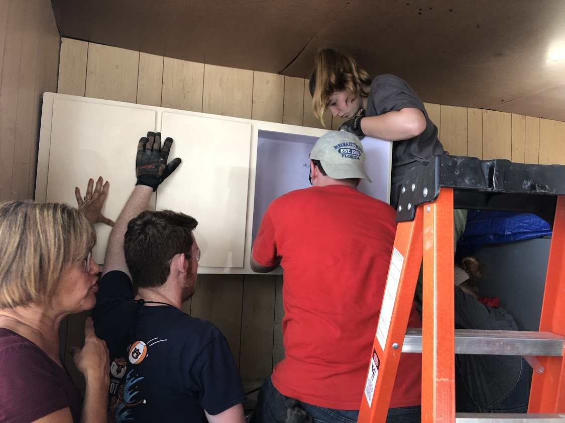Team Hot Pants (Ben Gourley, Josh Ellis, Megan Kucera install/replace a cabinet