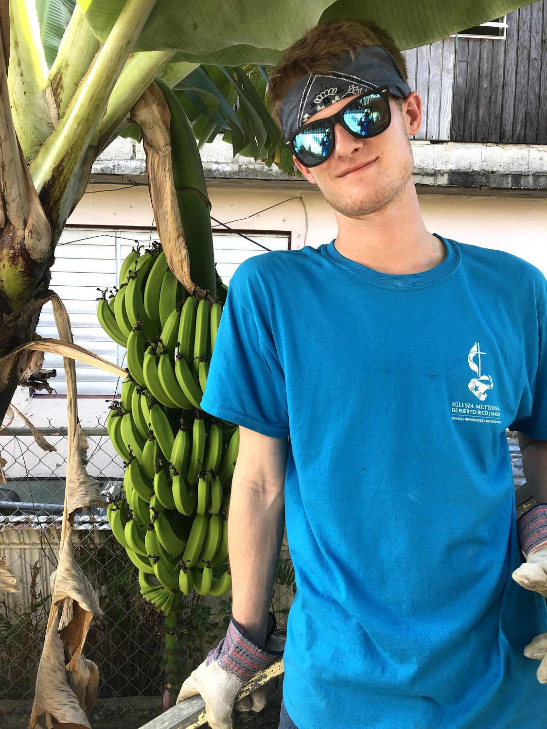 Richard White poses by a banana tree that was in the homeowner's backyard. Photo creds to JT Mercer